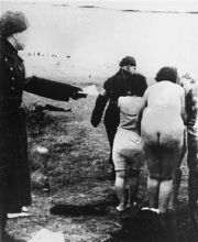 A Latvian guard leads Jewish women to the execution site